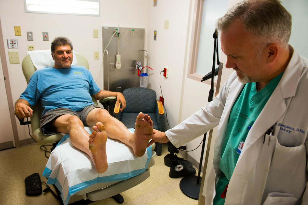 . Dr. Eric Espensen checks the legs and feet of Paul Vinci at  the Amputation Prevention Center at Valley Presbyterian Hospital, Friday, August 8, 2014. Vinci is diabetic with various foot ailments. (Photo by Michael Owen Baker/Los Angeles Daily News)