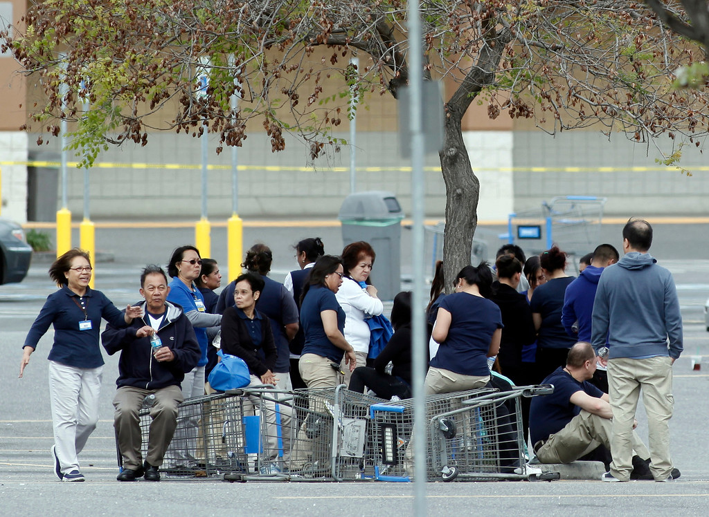. Walmart employees huddle in the parking lot outside the store on Story Road in San Jose, Calif., after a vehicle drove into the building and a driver reportedly began assaulting people in the store Sunday, March 31, 2013. (Karl Mondon/Staff)