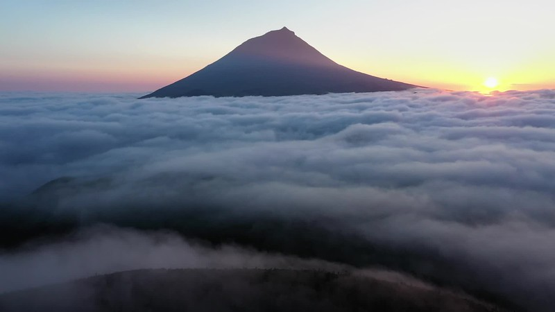 Available in 4K - Aerial video clip with magical sunset over a low cloud layer covering Pico Island, The Azores
