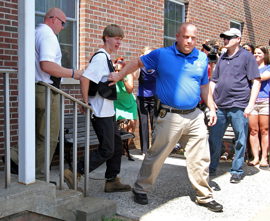 . Charleston, S.C., shooting suspect Dylann Storm Roof, second from left, is escorted from the Shelby Police Department in Shelby, N.C., Thursday, June 18, 2015. Roof is a suspect in the shooting of several people Wednesday night at the historic The Emanuel African Methodist Episcopal Church in Charleston, S.C. (AP Photo/Chuck Burton)