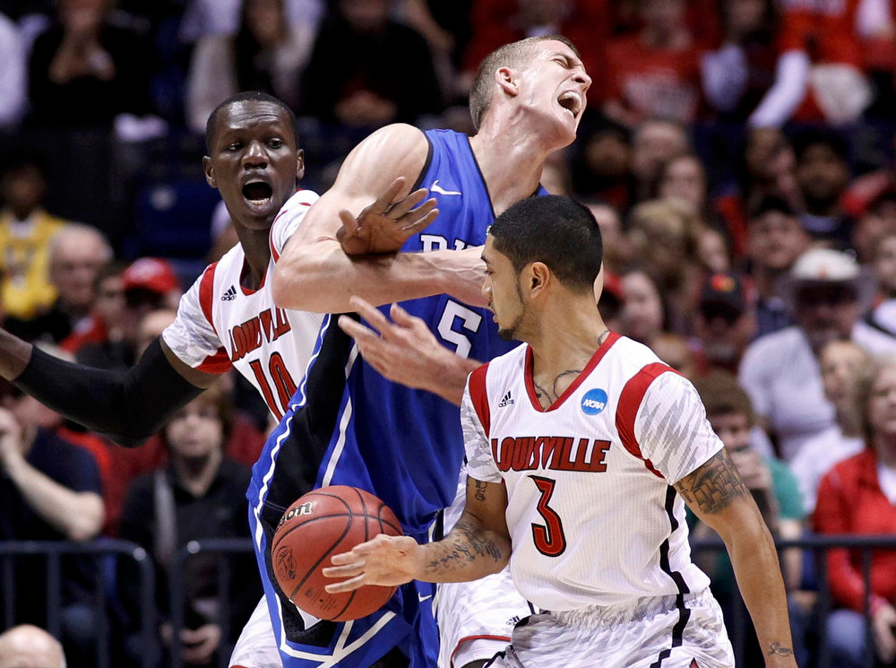 . Duke Blue Devils forward Mason Plumlee (5) is fouled by Louisville Cardinals center Gorgui Dieng (L) as Louisville guard Peyton Siva (3) defends in the first half during their Midwest Regional NCAA men\'s basketball game in Indianapolis, Indiana, March 31, 2013. REUTERS/Jeff Haynes
