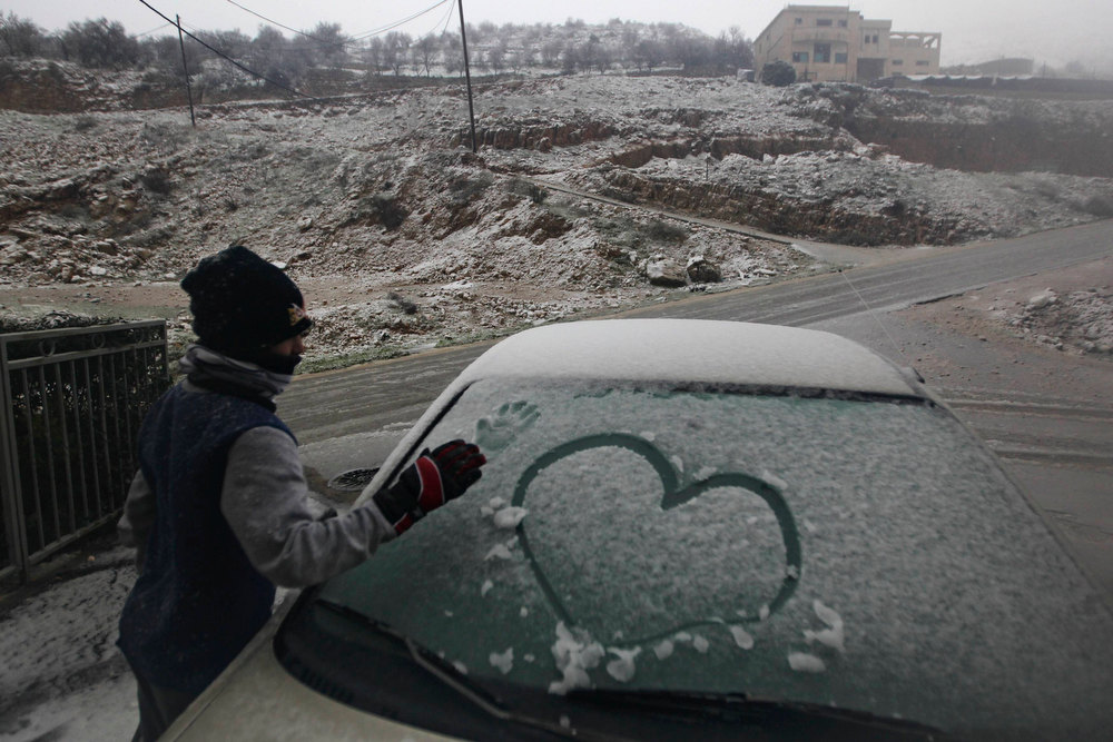 Description of . A boy makes a print of his hand on a car windscreen covered with snow before clearing it, during stormy weather in the Druze village of Majdal Shams on the Golan Heights January 8, 2013. REUTERS/Ammar Awad
