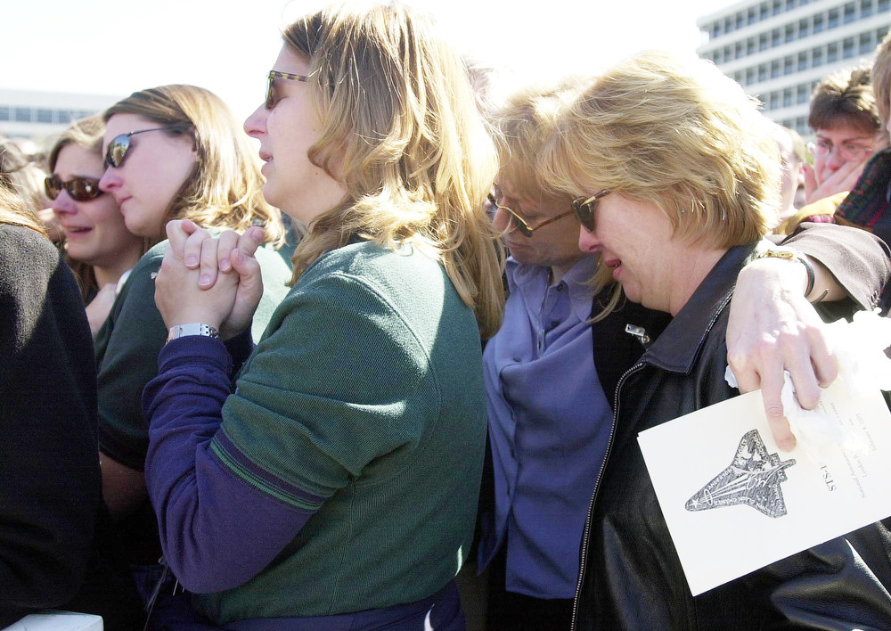 . Members of the NASA STS-107 training team huddle together as they all cry at the end of the memorial service for the crew of the space shuttle Columbia Tuesday, Feb. 4, 2003, in Houston. The training team worked with the Columbia crew to prepare them for the flight. (AP Photo/Ed Sackett, Pool)
