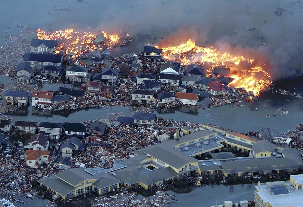 . Houses are shown in flame while the Natori river floods over the surrounding area by tsunami tidal waves in Natori city, Miyagi Prefecture, northern Japan, March 11, 2011, after strong earthquakes hit the area. (AP Photo/Yasushi Kanno, The Yomiuri Shimbun)