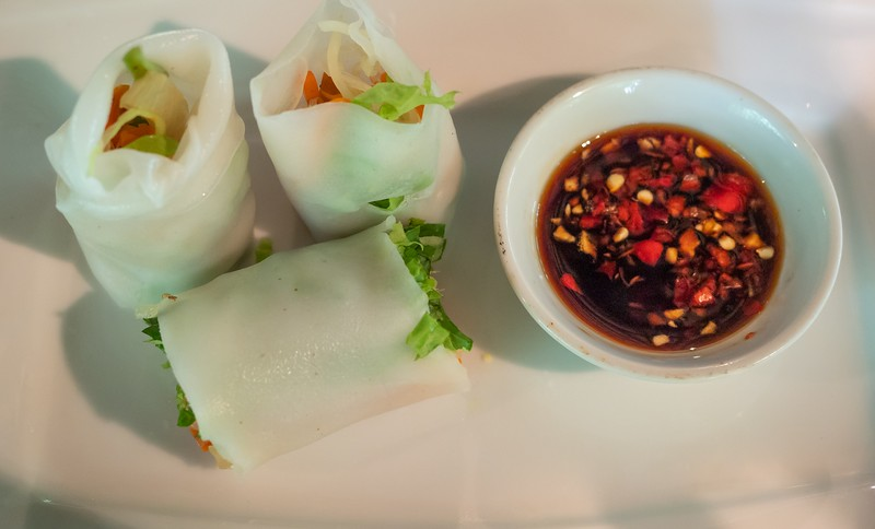 Three Spring Rolls on a plate with red dipping sauce.