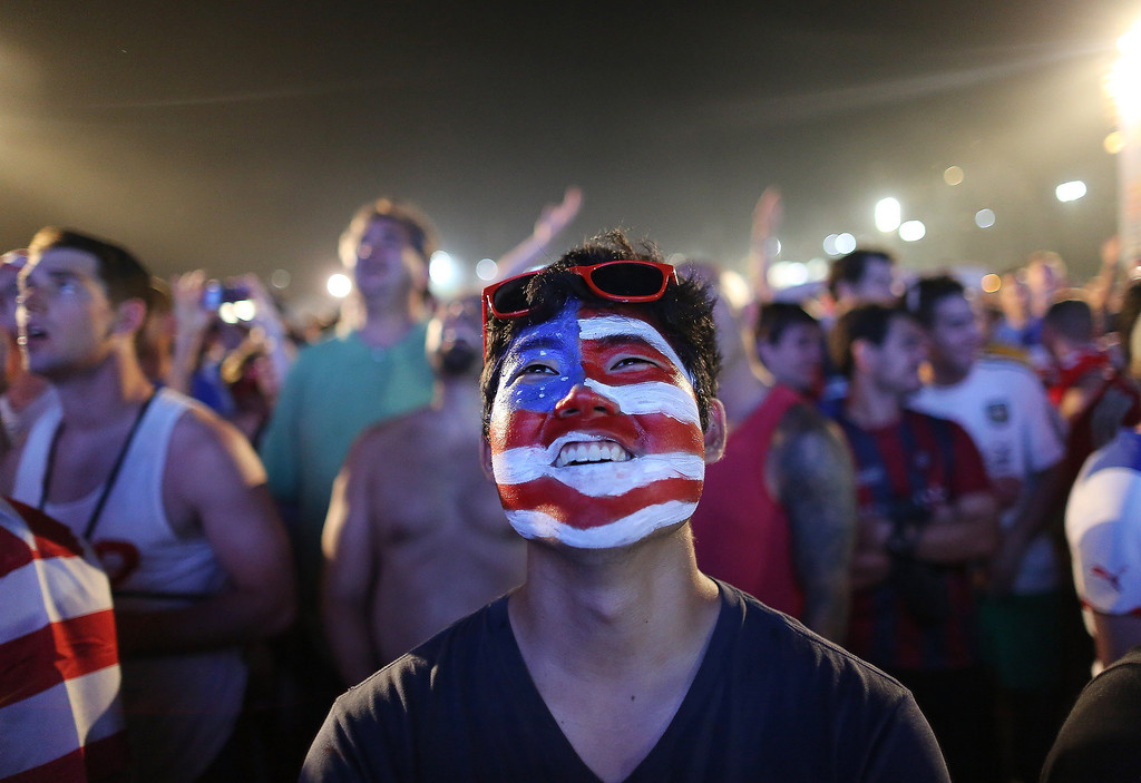 . A soccer fan of the U.S. national soccer team watches a live broadcast of the soccer World Cup match between USA and Ghana, inside the FIFA Fan Fest area on Copacabana beach, Rio de Janeiro, Brazil, Monday, June 16, 2014. (AP Photo/Leo Correa)