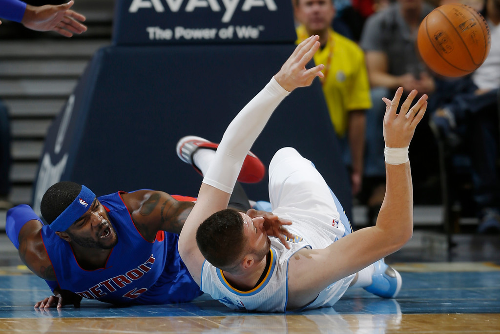 . Detroit Pistons forward Josh Smith, left, battles for control of a loose ball with Denver Nuggets center Jusuf Nurkic, of Bosnia Herzegovina, in the first quarter of an NBA basketball game in Denver on Wednesday, Oct. 29, 2014. (AP Photo/David Zalubowski)
