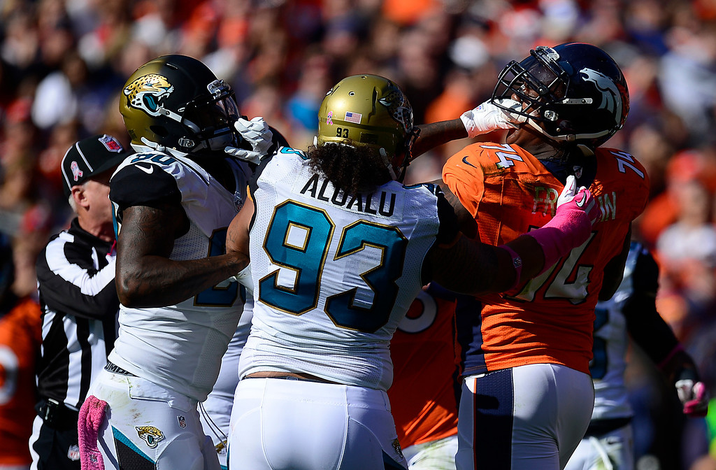 . DENVER, CO - OCTOBER 13: Jacksonville Jaguars defensive end Andre Branch (90) grabs Denver Broncos tackle Orlando Franklin (74) by the face mask in the first quarter. Franklin was penalized for unnecessary roughness. The Denver Broncos take on the Jacksonville Jaguars at Sports Authority Field at Mile High in Denver on October 13, 2013. (Photo by AAron Ontiveroz/The Denver Post)