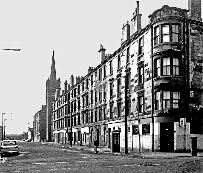 Golspie St from Langlands Rd.  The picturesque pre-industrial village of Govan viewed from the east or from Partick was a favoured subject for 18th and 19th century landscape artists (SCRAN has many examples), and the focal point of the view is generally a church with a neat tower and spire - Govan Old Parish Church, latterly the 1828 building, which was modelled on the Shakespeare church in Stratford-upon-Avon. This focal point was lost in 1884 when the church was deemed too small for the expanding congregation and was replaced by the present towerless building (a tower was planned but the money ran out). However, with commendable enterprise the old church was dismantled stone by stone, carted a few hundred yards, and re-erected in Golspie St as Elderpark Parish Church.     February 1974