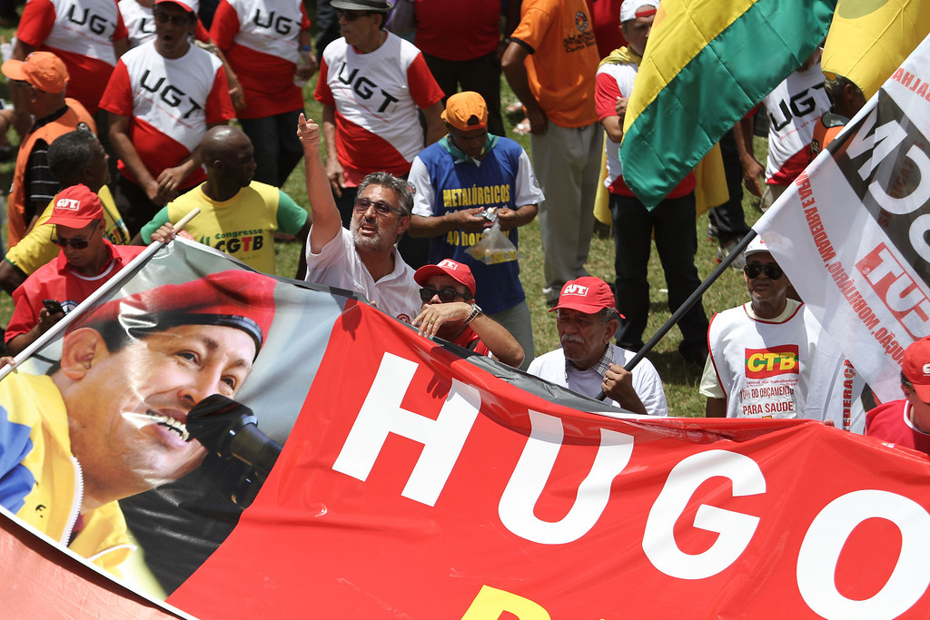 . Workers gather for a tribute to Venezuela\'s late President Hugo Chavez during a march by the Central Labor Union in Brasilia, Brazil, Wednesday, March 6, 2013. Chavez, who died Tuesday at age 58, was seen as a hero by some for his socialist programs, his anti-U.S. rhetoric and gifts of cut-rate oil. Others considered him a bully who repressed his opponents. (AP Photo/Eraldo Peres)