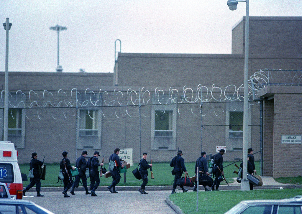 . Law enforcement officers dressed in riot gear walk along the fence line at the entrance to the Southern Ohio Correctional Facility in Lucasville, Ohio, April 12, 1993. Prisoners on one of the cell blocks rioted yesterday, killing five inmates and taking guards hostage. (AP Photo/Chris Kasson)