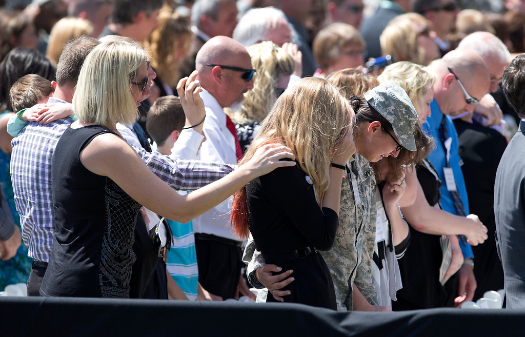 . Family members and friends comfort each other as the final roll call is called out during a memorial ceremony, Wednesday, April 9, 2014, at Fort Hood Texas, for those killed there in a shooting last week. (AP Photo/Carolyn Kaster)