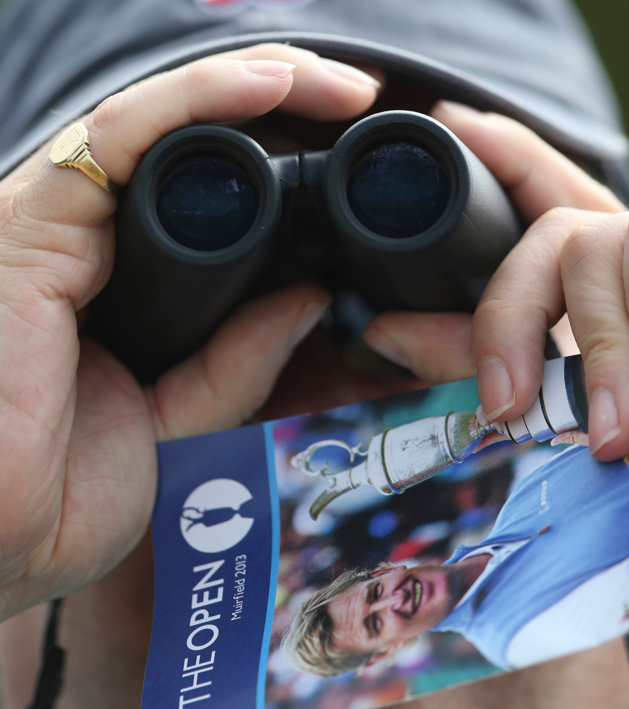 . A spectator watches the play through binoculars during the first round of the British Open Golf Championship at Muirfield, Scotland, Thursday July 18, 2013. (AP Photo/Scott Heppell)