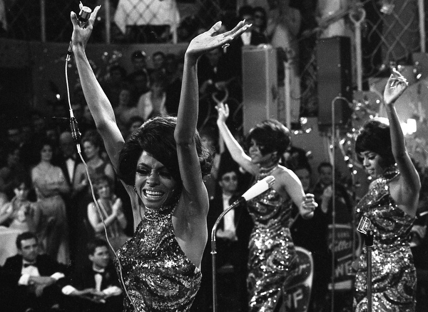""". The Supremes with Diana Ross, front, Cindy Birdsong and Mary Wilson dance with their arms in the air as they perform at the annual \""""Bal pare\"""" party in Munich, West Germany, January 21, 1968. The U.S. American singing trio was backed by the West German Rolf Hans Mueller big band and were celebrated with thundering applause. (AP Photo/Frings)"""