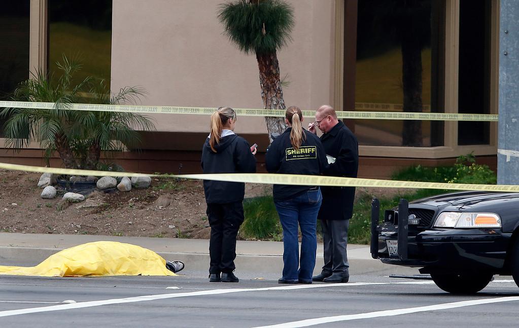 . Investigators stand next to a tarp covered body in Orange, Calif., Tuesday, Feb. 19, 2013. (AP Photo/Jae C. Hong)