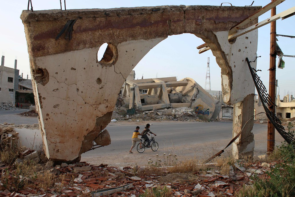 . A picture taken through an arch remaining from a detroyed building shows Syrian boys on a bicycle on May 14, 2016 in the southern Syrian city of Daraa. MOHAMAD ABAZEED/AFP/Getty Images