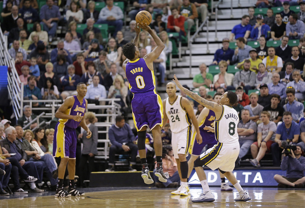 . Los Angeles Lakers\' Nick Young (0) shoots as Utah Jazz\'s Diante Garrett (8) looks on in the second half during an NBA basketball game Monday, April 14, 2014, in Salt Lake City, Utah. (AP Photo/Rick Bowmer)