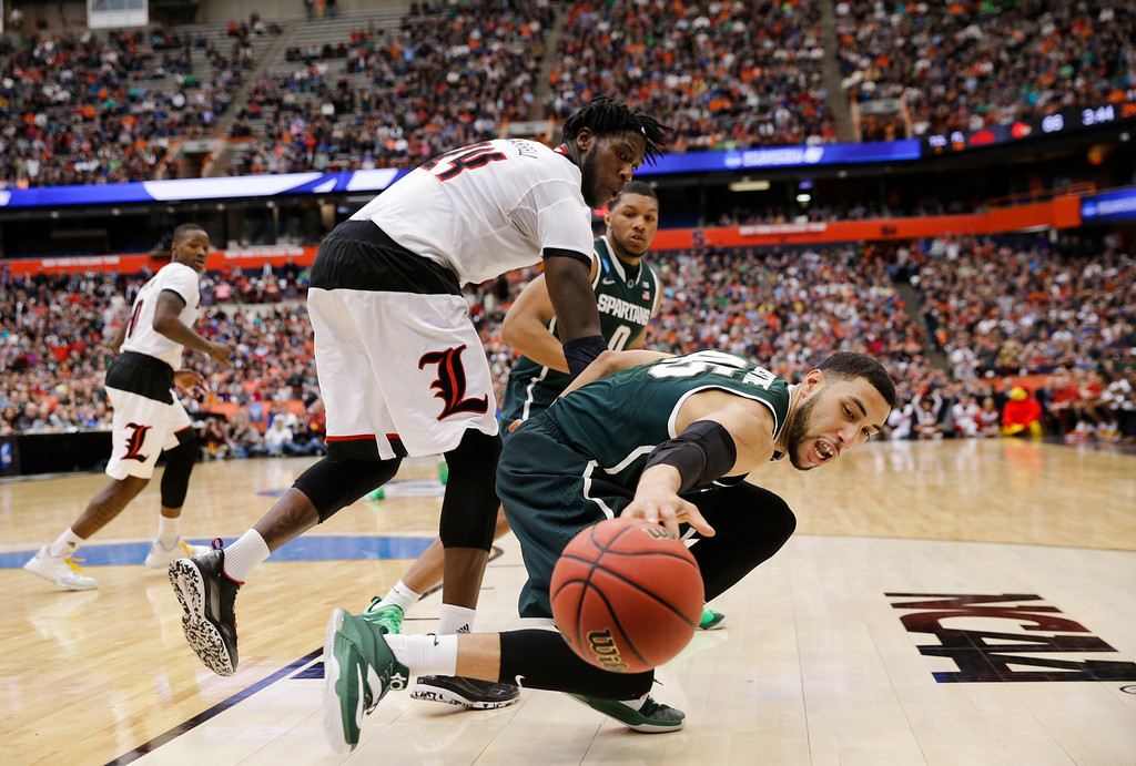 . Michigan State\'s Denzel Valentine (45) reaches for the ball as Louisville\'s Montrezl Harrell (24) watches during the overtime period in the NCAA men\'s college basketball tournament Sunday, March 29, 2015, in Syracuse, N.Y. Michigan State won the game 76-70. (AP Photo/Seth Wenig)