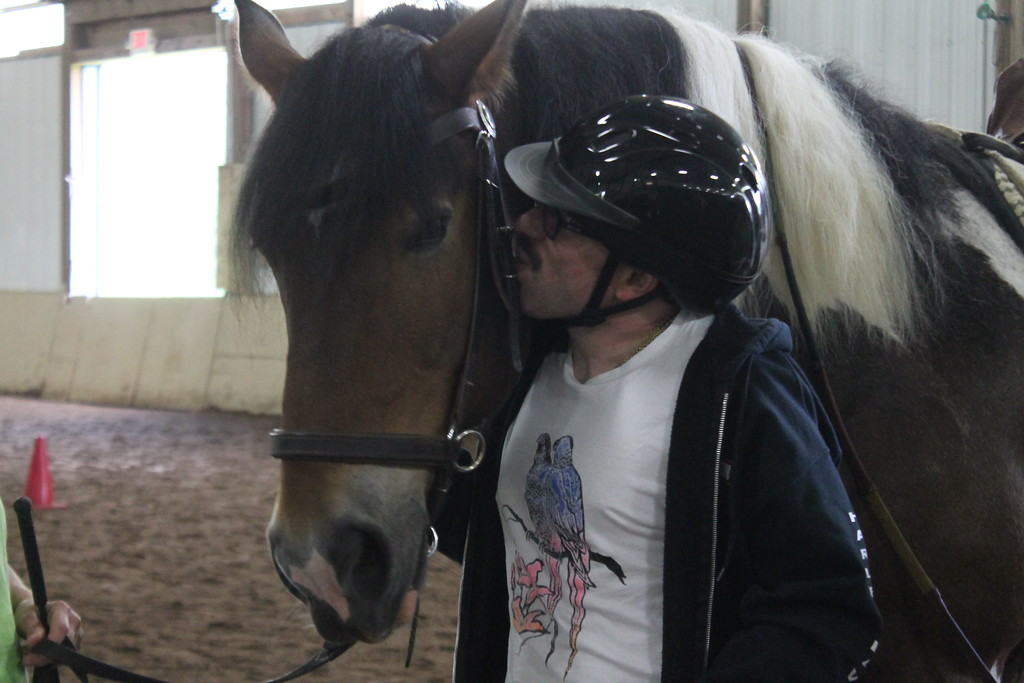 . Ed Probst a client of The Willoughby Branch,  shows his fondness for the horse he rode during an equine therapy exercise at Fieldstone Farm  by giving it a kiss afterwards. Kristi Garabrandt - The News-Herald