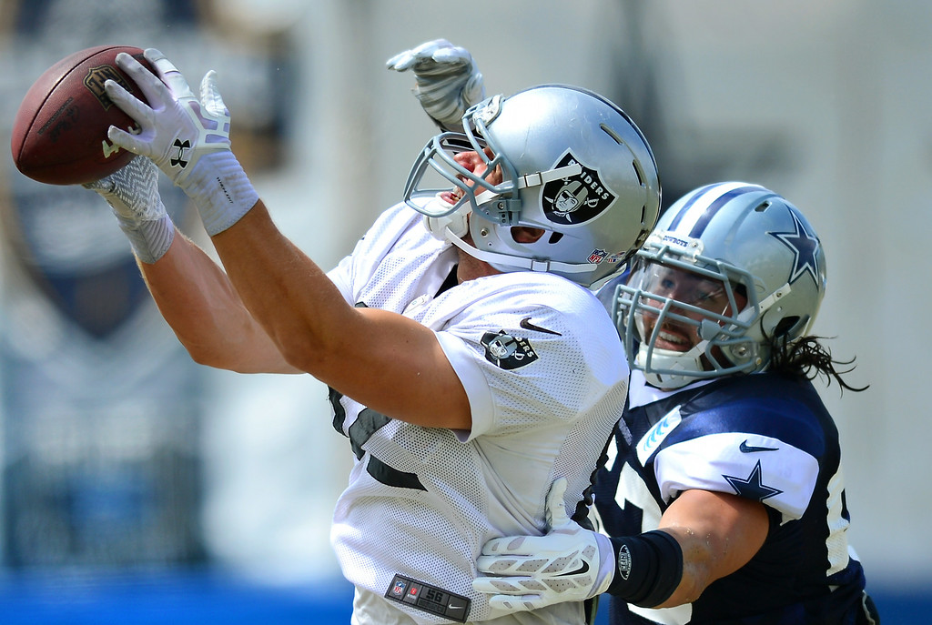 . Raider TE Jake Murphy catches a pass against Cowboy LB Cameron Lawrence at the Cowboys-Raiders practice in Oxnard, Wednesday, August 13, 2014. (Photo by Michael Owen Baker/Los Angeles Daily News)