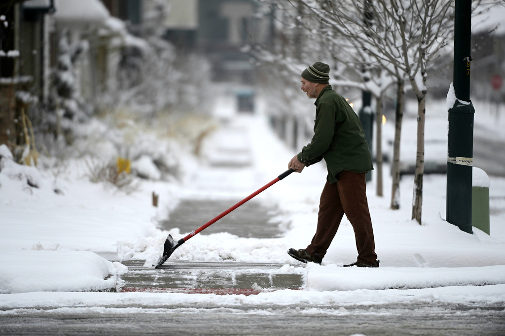 . David Beyer shovels snow and slush from his sidewalk near 23rd Ave and Spruce St. in Denver, Tuesday morning, April 16th, 2013. Andy Cross, The Denver Post