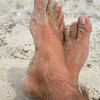 Man's feet crossed as he relaxes on the beach.