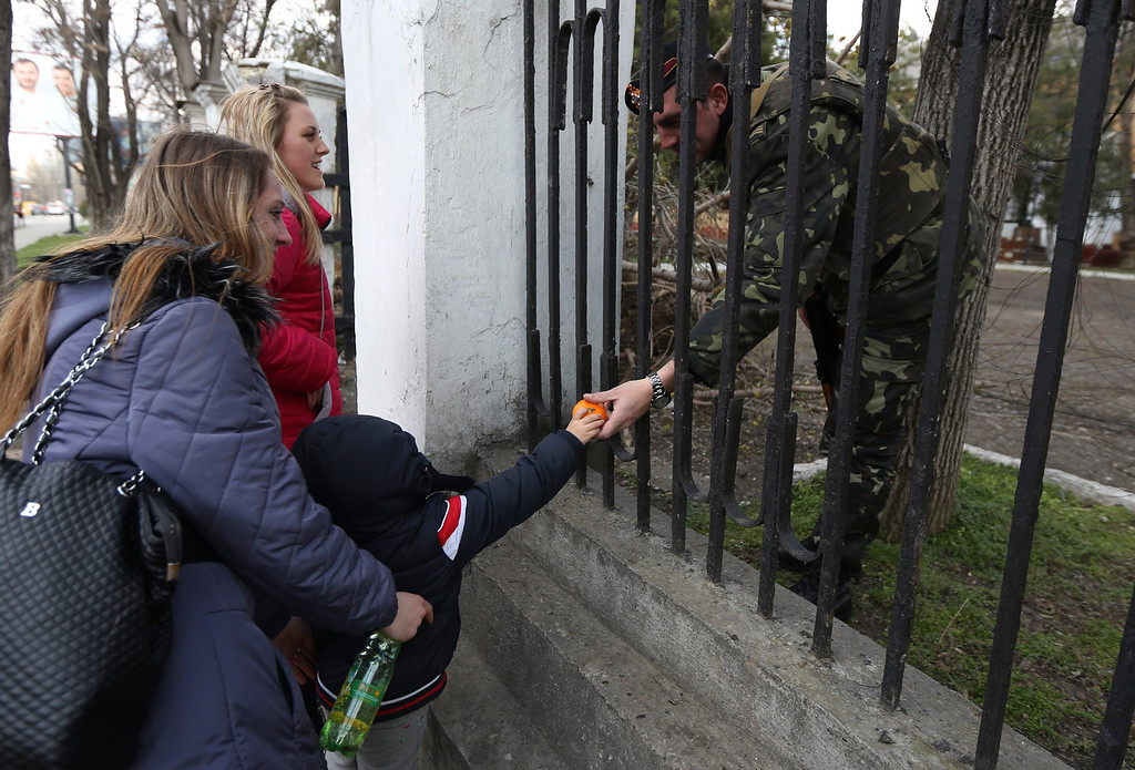 . A child gives fruit to a Ukrainian officer at the Ukrainian Military Prosecutor\'s Office in Simferopol, Crimea, Thursday, March 20, 2014. (AP Photo/Maxin Vetrov)