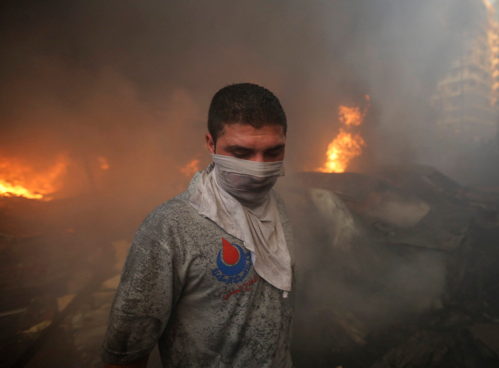 . A Hezbollah civil defense worker walks past a burned car at the site of a car bomb explosion in southern Beirut, Lebanon, Thursday, Aug. 15, 2013. The powerful car bomb ripped through a southern Beirut neighborhood that is a stronghold of the militant group Hezbollah on Thursday, killing people and trapping others in burning buildings, the media said. (AP Photo/Hussein Malla)