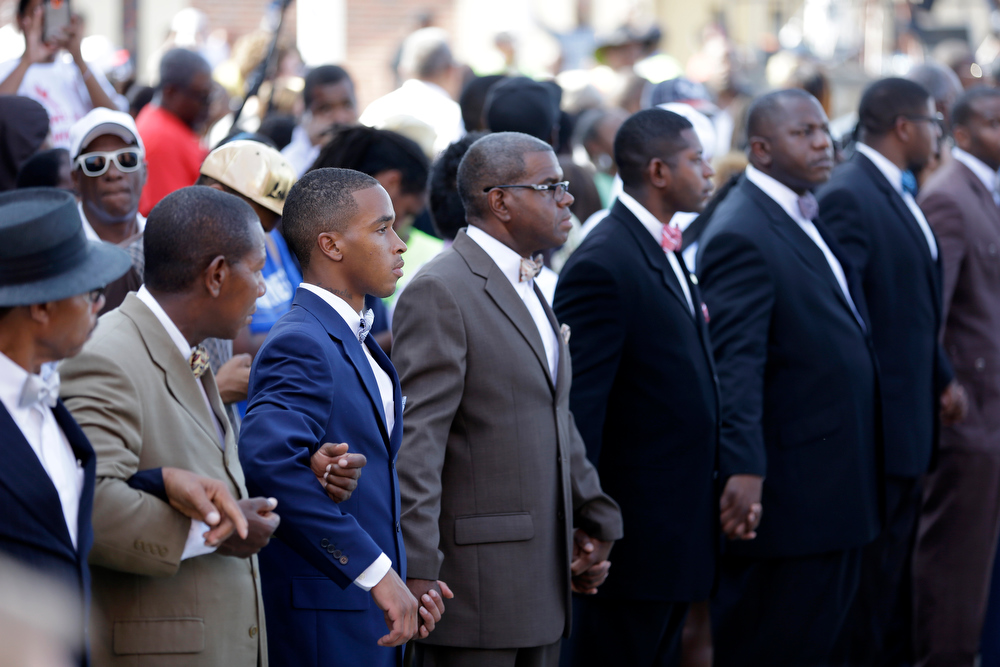 Description of . People line up to make a path for the families' and friends' arrival at Friendly Temple Missionary Baptist Church during the funeral for Michael Brown Monday, Aug. 25, 2014, in St. Louis. Brown, who is black, was unarmed when he was shot Aug. 9 by Officer Darren Wilson, who is white. A grand jury is considering evidence in the case and a federal investigation is also underway. (AP Photo/Jeff Roberson)