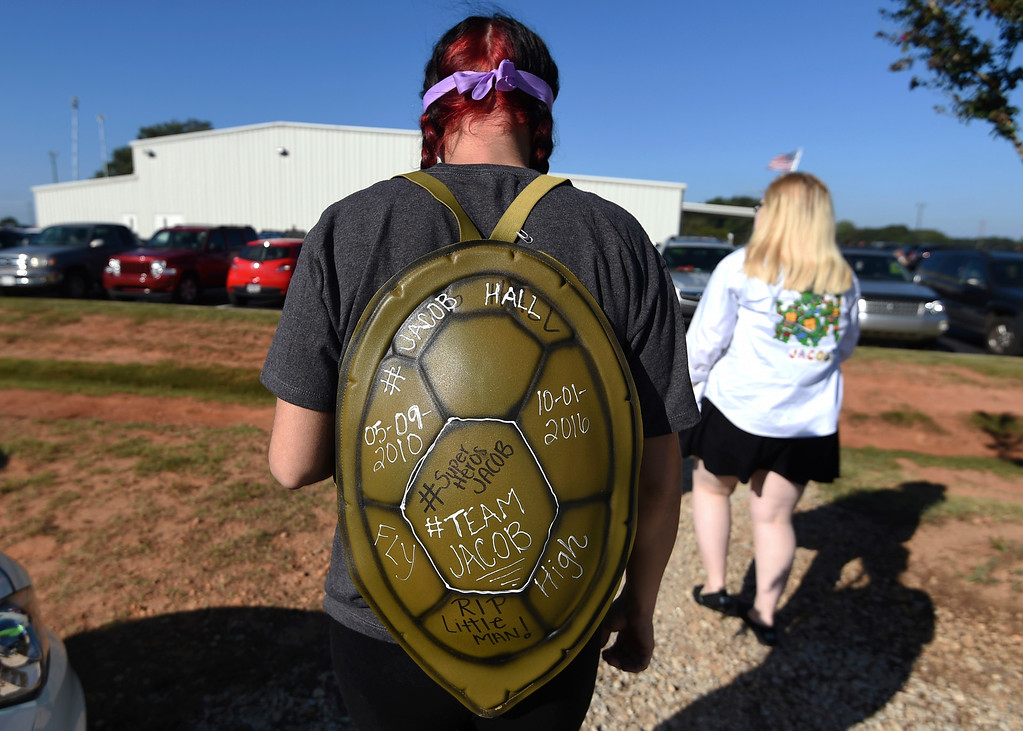 . Kortnie Lanclos, of Liberty, S.C., wears a Teenage Mutant Ninja Turtles shell before a superhero-themed funeral service for Jacob Hall at Oakdale Baptist Church on Wednesday, Oct. 5, 2016, in Townville, S.C.   Jacob\'s family has encouraged people to celebrate his life by dressing as the superheroes he loved.  A 14-year-old boy killed his own father, then drove to Townville Elementary and fired on two children and a teacher as recess began.  Jacob died Saturday.  (AP Photo/Rainier Ehrhardt)