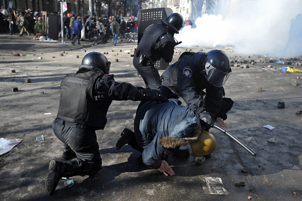 . Riot police detains a protester during an anti-government protest in downtown Kiev, Ukraine, 18 February 2014. A least three protesters were killed in clashes with police on 18 February, Ukrainian opposition activists say. Violence erupted in the Ukrainian capital after anti-government protesters broke through a police cordon in front of parliament. Protester marched toward the parliament to demand constitutional reforms that would curb the powers of President Viktor Yanukovych. Ukraine has been mired in political crisis since November after the government backed away from a trade agreement with the European Union and signed a 15-billion-dollar loan deal with Russia instead.  EPA/ALEXEY FURMAN
