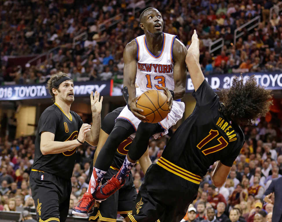 . New York Knicks\' Jerian Grant, center, drives to the basket against Kevin Love, left, and Anderson Varejao, from Brazil, during the first half of an NBA basketball game Wednesday, Nov. 4, 2015, in Cleveland. (AP Photo/Tony Dejak)