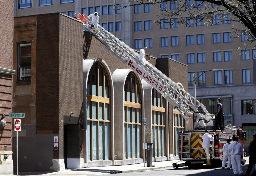 . An FBI investigator, center, walks down a fire truck ladder with a bag from a building at the corner of Boylston Street and Fairfield Street , Wednesday, April 17, 2013, in Boston. Investigators in white jumpsuits fanned out across the streets, rooftops and awnings around the blast site in search of clues on Wednesday. (AP Photo/Julio Cortez)