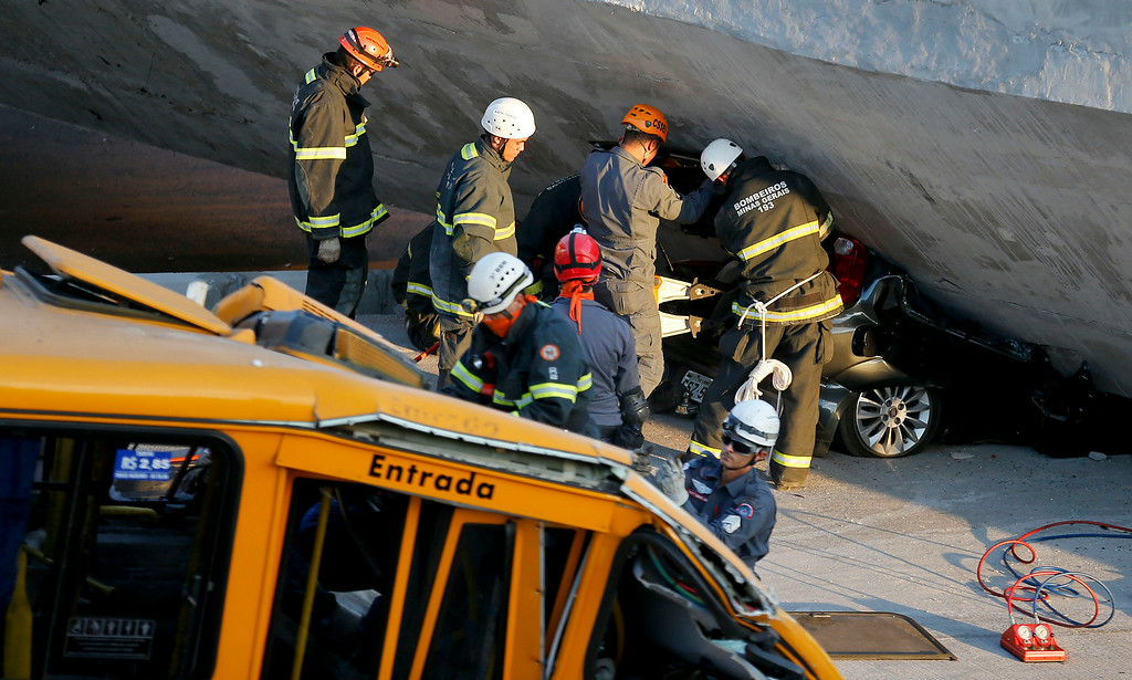 . Fire department personnel work to retrieve a car from underneath a collapsed bridge in Belo Horizonte, Brazil, Thursday, July 3, 2014. The overpass under construction collapsed Thursday in the Brazilian World Cup host city. The incident took place on a main avenue, the expansion of which was part of the World Cup infrastructure plan but, like most urban mobility projects related to the Cup, was not finished on time for the event. (AP Photo/Victor R. Caivano)