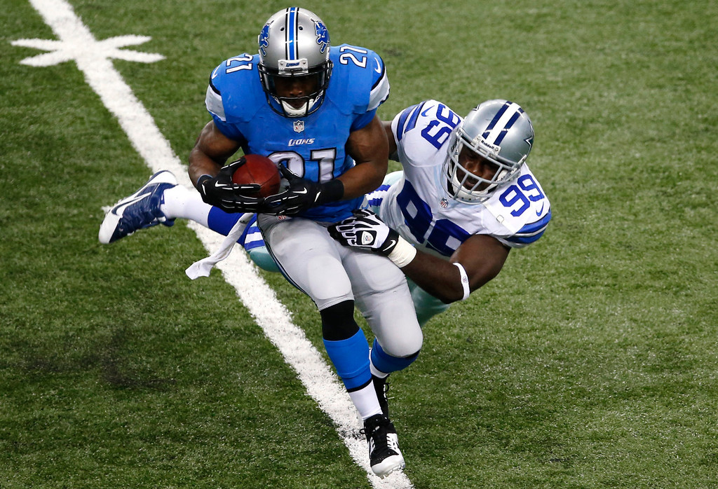 . Detroit Lions running back Reggie Bush (21) is brought down by Dallas Cowboys defensive end George Selvie (99) in the first half of an NFL football game in Detroit, Sunday, Oct. 27, 2013. (AP Photo/Paul Sancya)