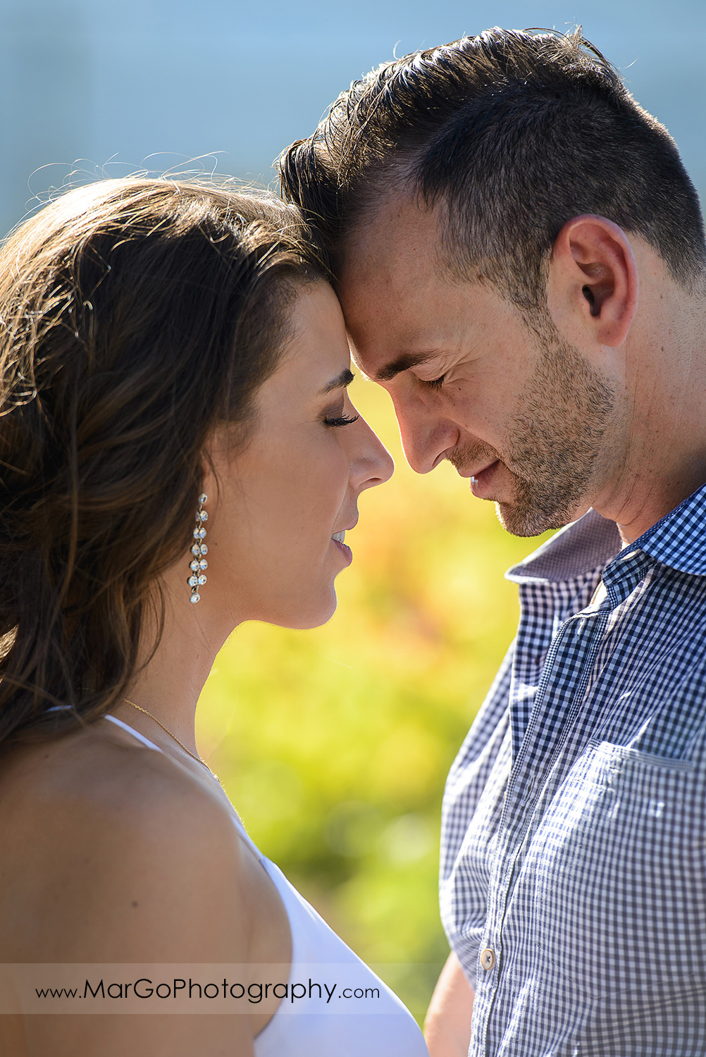 close-up portrait of woman in white top and man in blue shirttouching foreheads with eyes closed during Napa Valley engagement session at Grgich Hills Estate in Rutherford