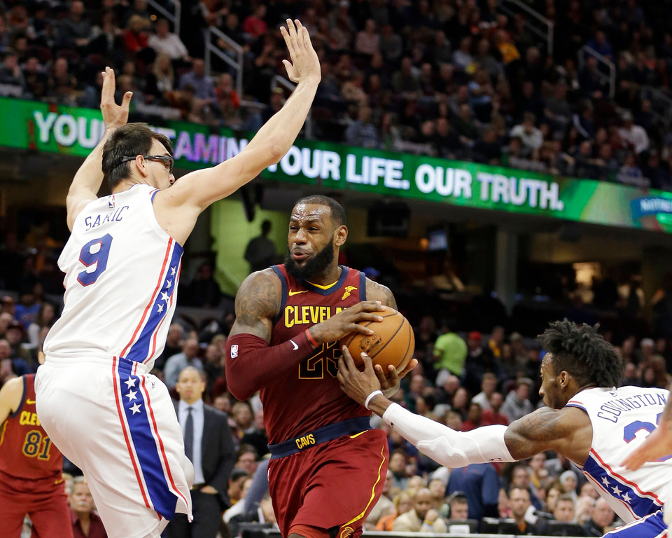 . Cleveland Cavaliers\' LeBron James drives between Philadelphia 76ers\' Dario Saric and Robert Covington during the second half of an NBA basketball game Saturday, Dec. 9, 2017, in Cleveland. The Cavaliers won 105-98. (AP Photo/Tony Dejak)