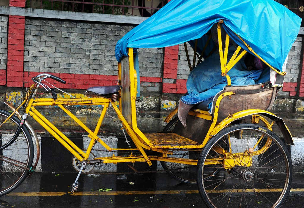 . An Indian rickshaw puller takes a nap on his cart during heavy rains in Chennai on May 18, 2016.  While northern and central India is reeling under high summer temperatures and drought conditions, southern and eastern parts of the country have been struck with heavy rainfall ahead of the onset of the monsoon season.  / AFP PHOTO / ARUN SANKAR/AFP/Getty Images
