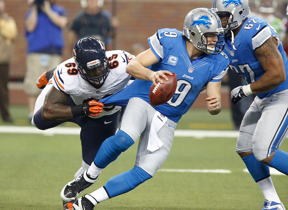 . Detroit Lions quarterback Matthew Stafford (9) pulls away from Chicago Bears defensive tackle Henry Melton (69) during the first quarter of an NFL football game at Ford Field in Detroit, Sunday, Dec. 30, 2012. (AP Photo/Duane Burleson)