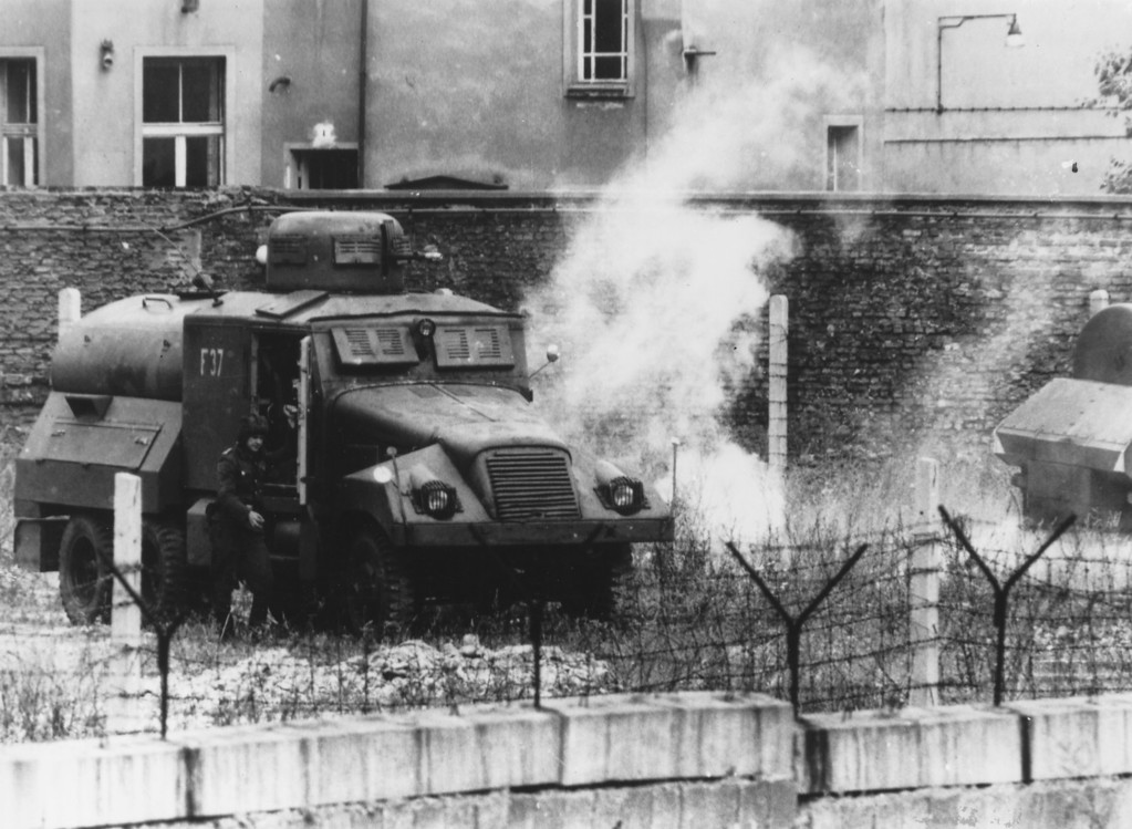 . A tear gas grenade explodes next to an East German armored car during riots on the first anniversary of the building of the Berlin Wall.  (Photo by Keystone/Getty Images)