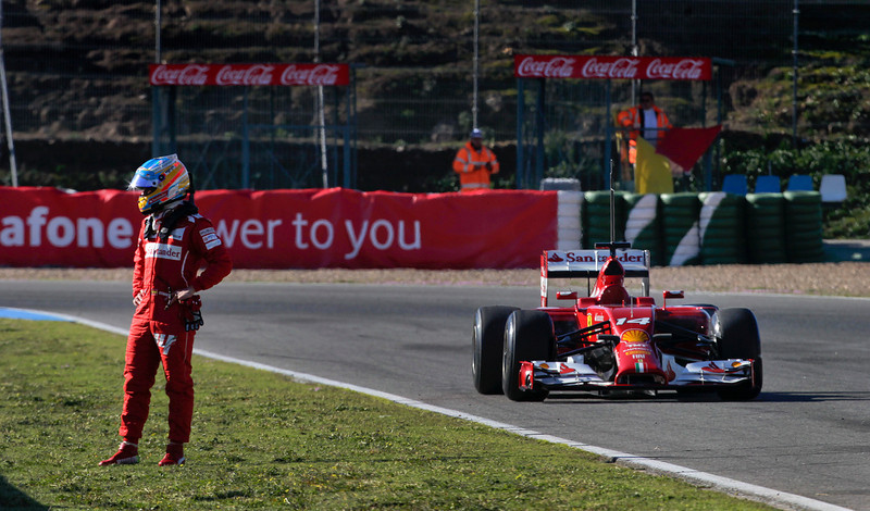 . Fernando Alonso of Spain and Ferrari stands near the new F14T car after it stopped on a practice lap, during the 2014 Formula One Testing at the Circuito de Jerez,  Thursday, Jan. 30, 2014, in Jerez de la Frontera, Spain. (AP Photo/Miguel Angel Morenatti)
