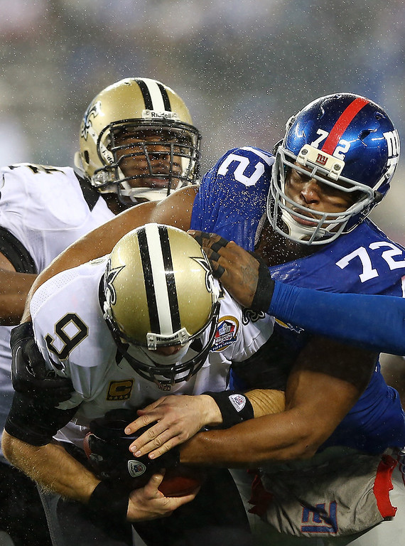 . Drew Brees #9 of the New Orleans Saints is sacked by  Osi Umenyiora #72 of the New York Giants on December 9, 2012 at MetLife Stadium in East Rutherford, New Jersey.  (Photo by Elsa/Getty Images)