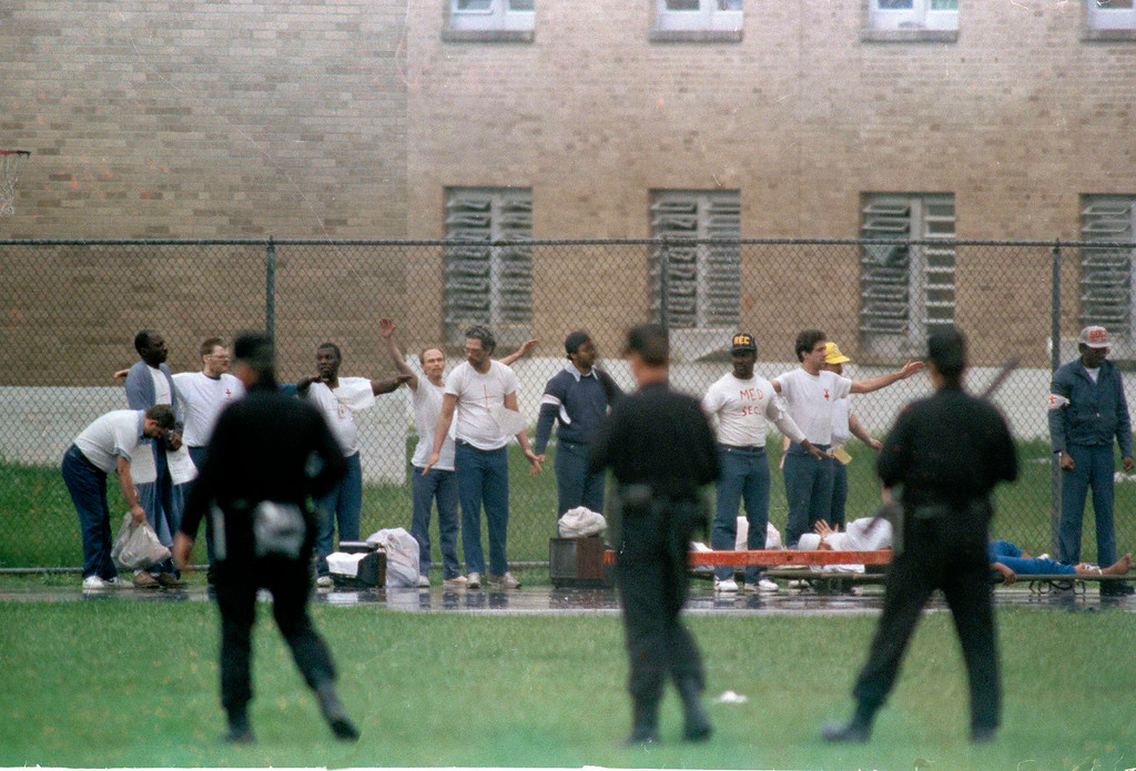 . Inmates raise their hands in surrender as armed guards watch on the recreation yard of Southern Ohio Correctional Facility in Lucasville, Ohio, April 21, 1993.  The 10-day siege at the prison ended Wednesday.  (AP Photo/Lennox McLendon)