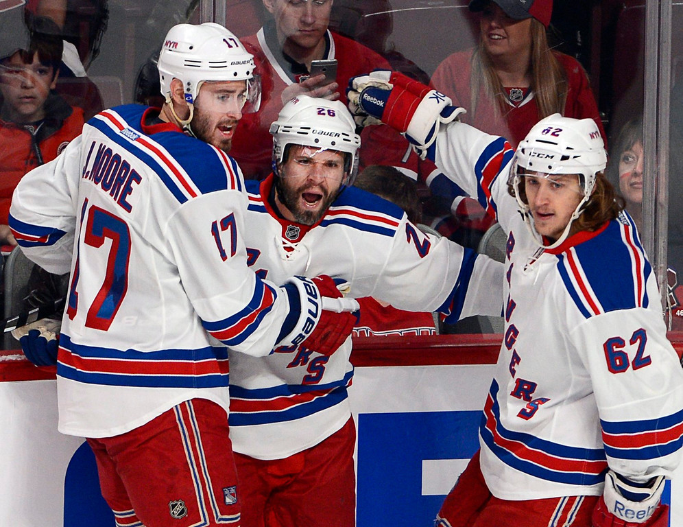 . New York Rangers right wing Martin St. Louis (26) celebrates with teammates John Moore and Carl Hagelin after scoring against the Montreal Canadiens during the first period in Game 1 of the Eastern Conference finals in the NHL hockey Stanley Cup playoffs in Montreal on Saturday, May 17, 2014. The Rangers won 7-2. (AP Photo/The Canadian Press, Ryan Remiorz)