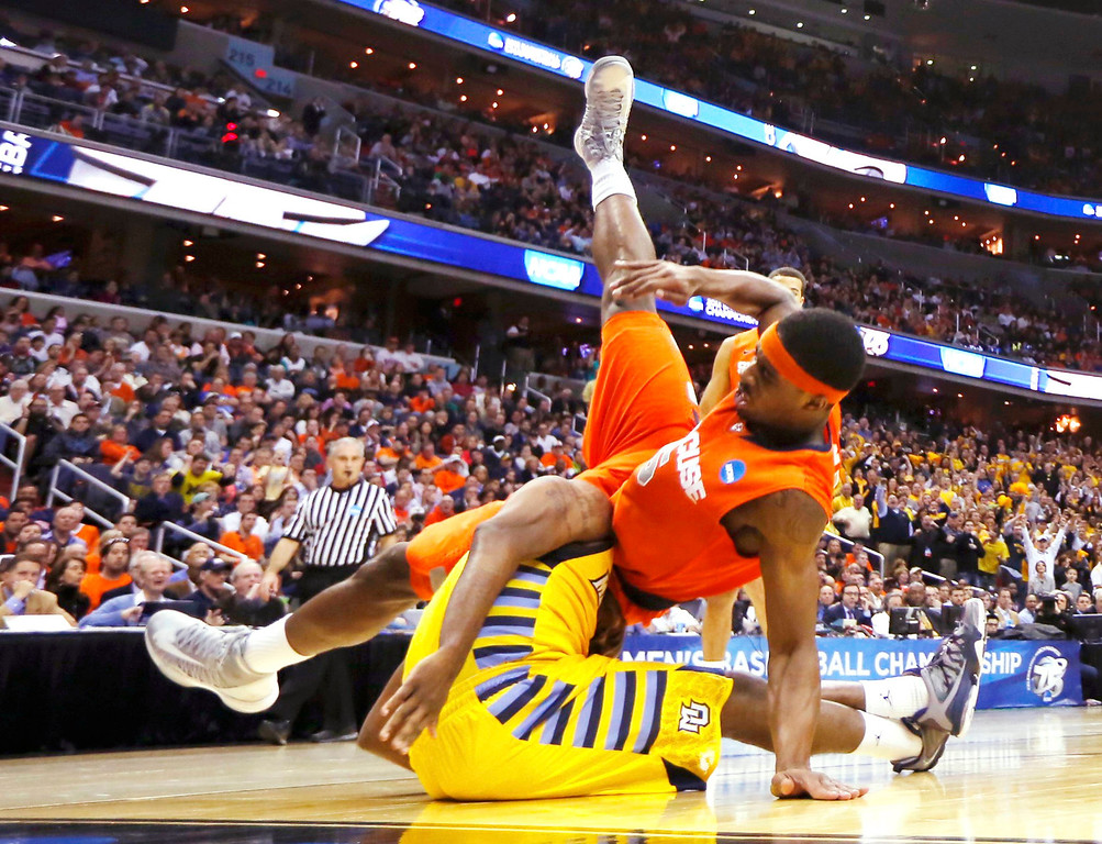 . Syracuse Orange forward C.J. Fair (top) falls on Marquette Golden Eagles guard Junior Cadougan after he made a basket during the first half in their East Regional NCAA men\'s basketball game in Washington, March 30, 2013. REUTERS/Jason Reed