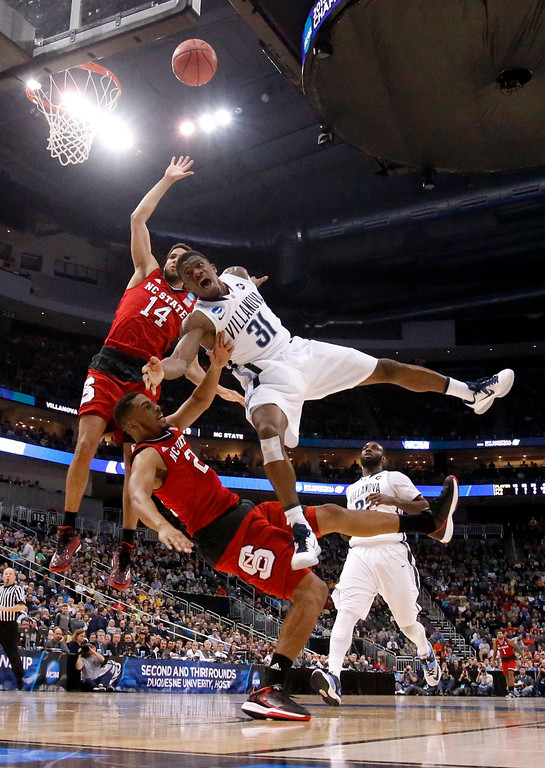 . Villanova\'s Dylan Ennis (31) shoots as North Carolina State\'s Ralston Turner, bottom and Caleb Martin (14) defend during the first half of an NCAA tournament third-round college basketball game, Saturday, March 21, 2015, in Pittsburgh. (AP Photo/Gene J. Puskar)