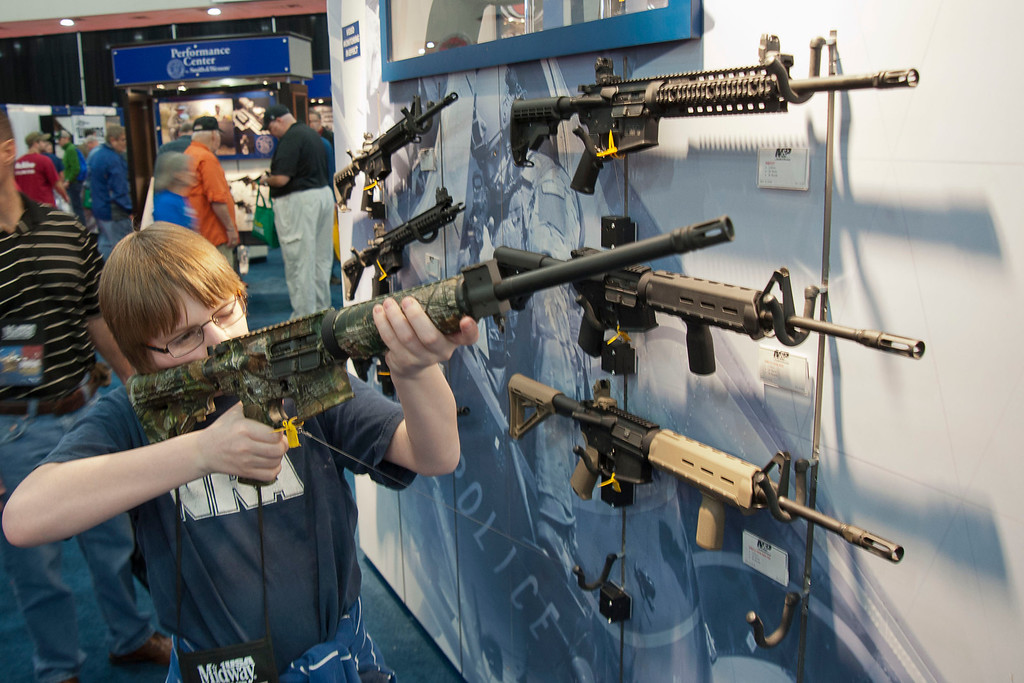 . A young man who chose not to give his name sizes-up an assault style rifle during the National Rifle Association\'s annual convention Friday, May 3, 2013 in Houston. (AP Photo/Steve Ueckert)
