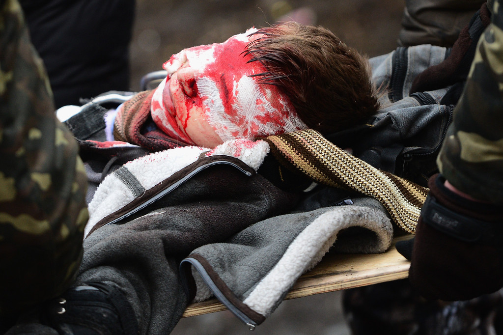 . Anti-government protesters carry the injured during continued clashes with police in Independence square, despite a truce agreed between the Ukrainian president and opposition leaders on February 20, 2014 in Kiev, Ukraine.  (Photo by Jeff J Mitchell/Getty Images)