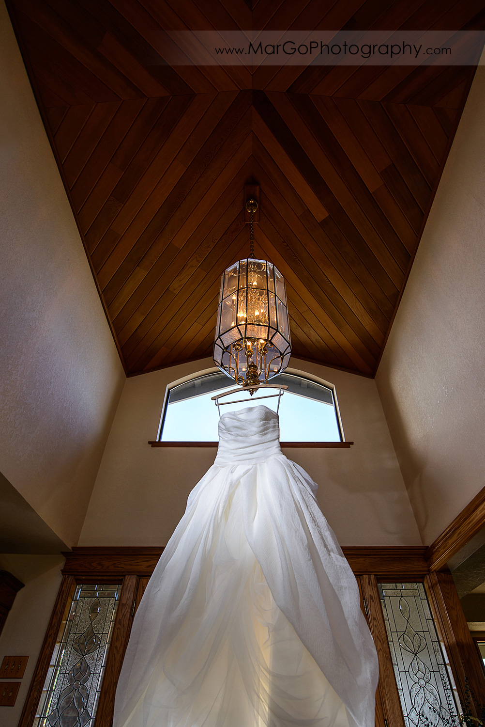 wedding dress hanging from wood ceiling