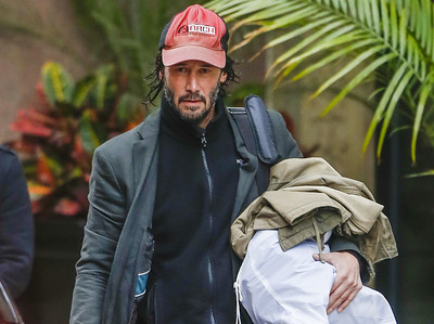 EXC: Keanu Reeves Carries Own Luggage Disheveled In Canada
